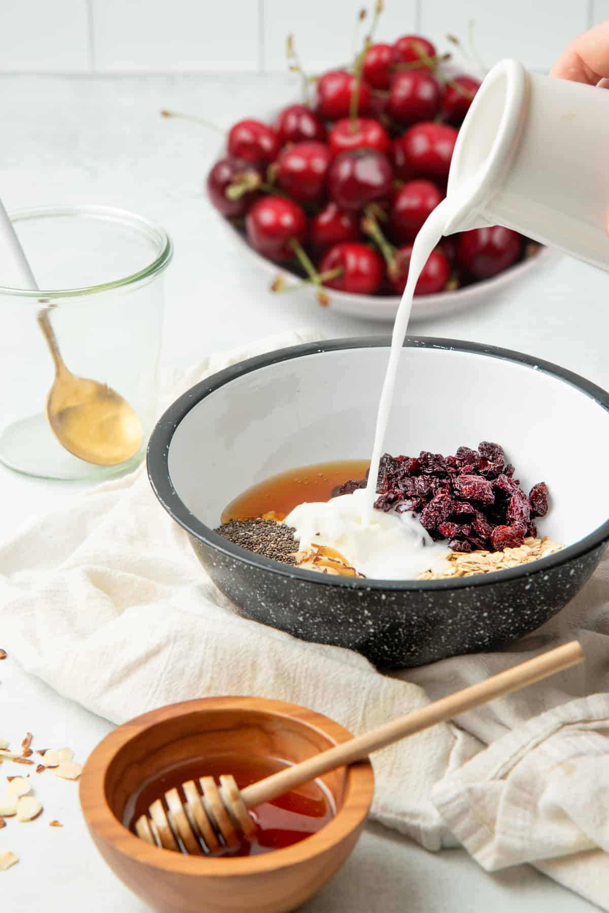 A pitcher pours milk into a mixing bowl full of oats, Greek yogurt, chia seeds, dried cherries, and other ingredients.