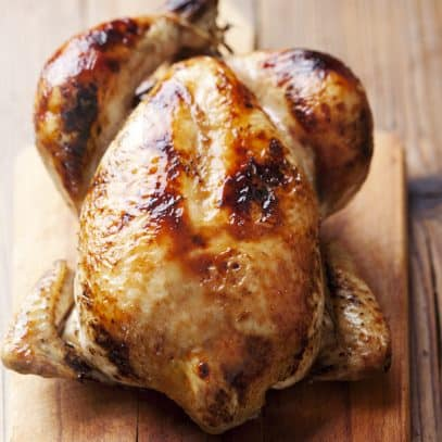 A rotisserie chicken sits on a wooden cutting board.