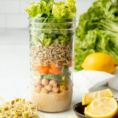 A tall mason jar with layered salad ingredients sits on a white counter in front of a white wall. Lemon slices sit next to the jar in a small black bowl.