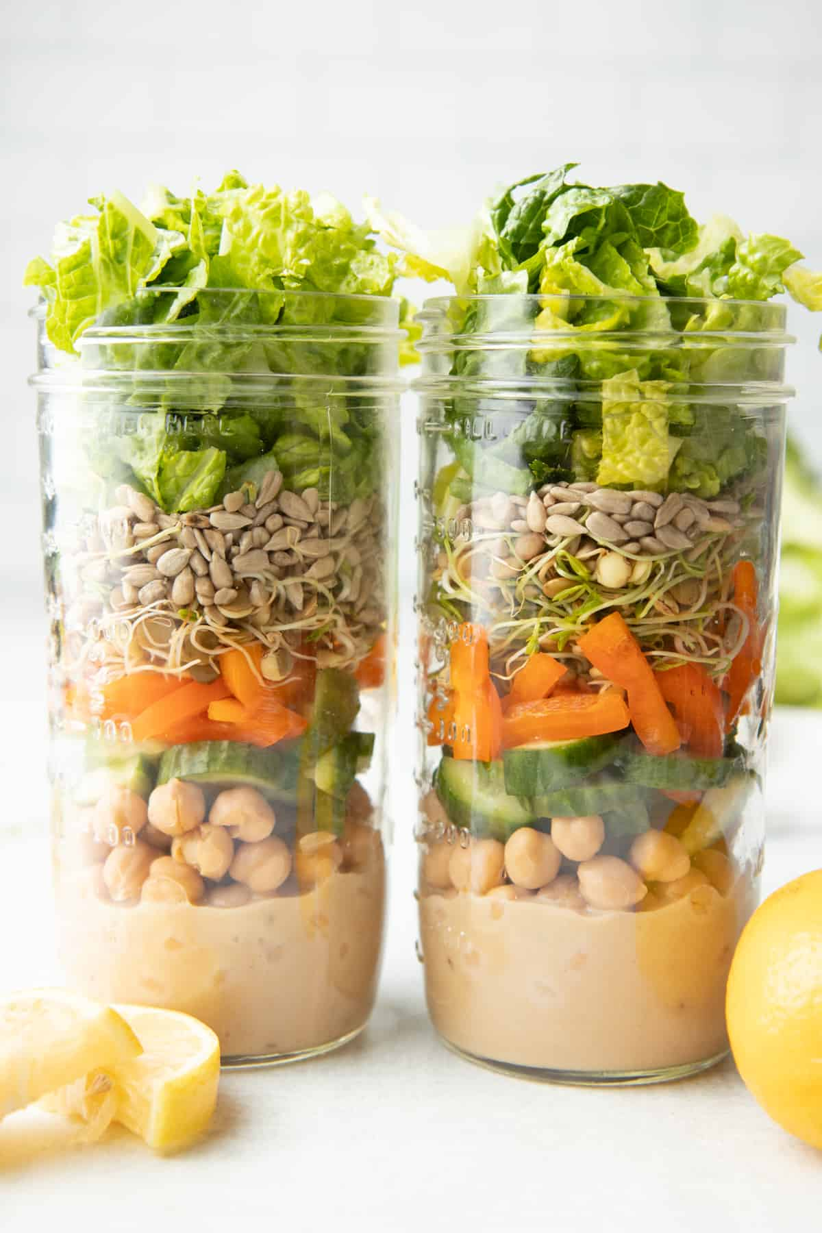 Two tall mason jars sit side by side. Jars are layered with dressing, chickpeas, cut vegetables, sprouts, seeds, and lettuce.