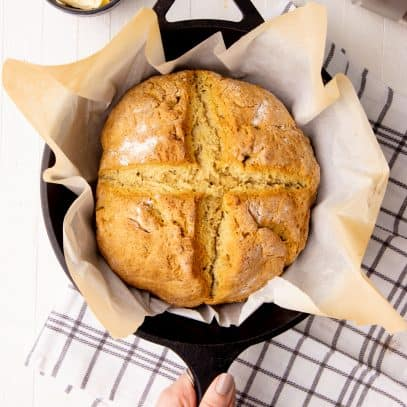 A round loaf of Irish soda bread rests in a cast iron skillet. A hand holds the handle of the pan.