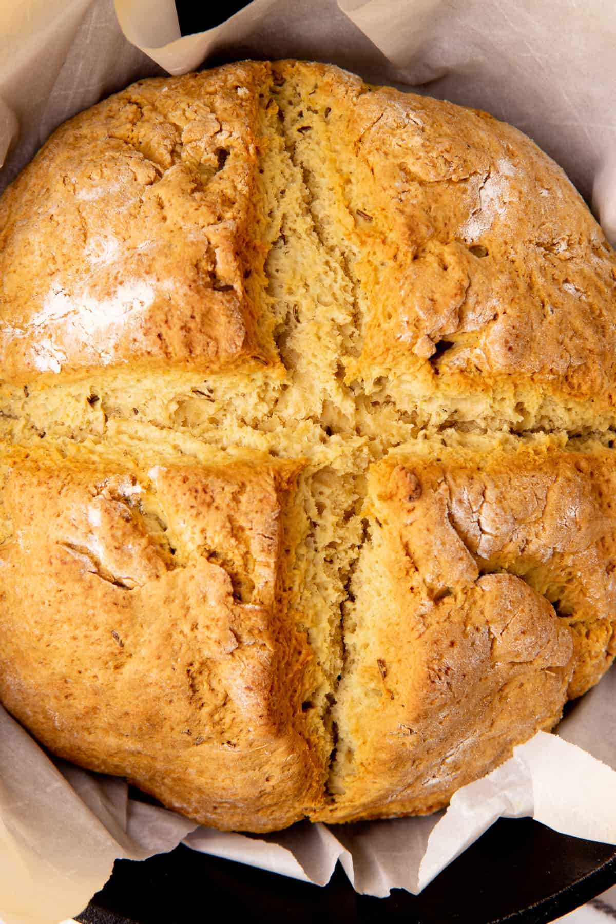 A round loaf of Irish soda bread rests in a cast iron skillet.