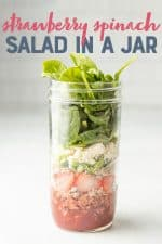 "Strawberry spinach salad layered in a glass mason jar. A text overlay reads ""Strawberry Spinach Salad in a Jar."""