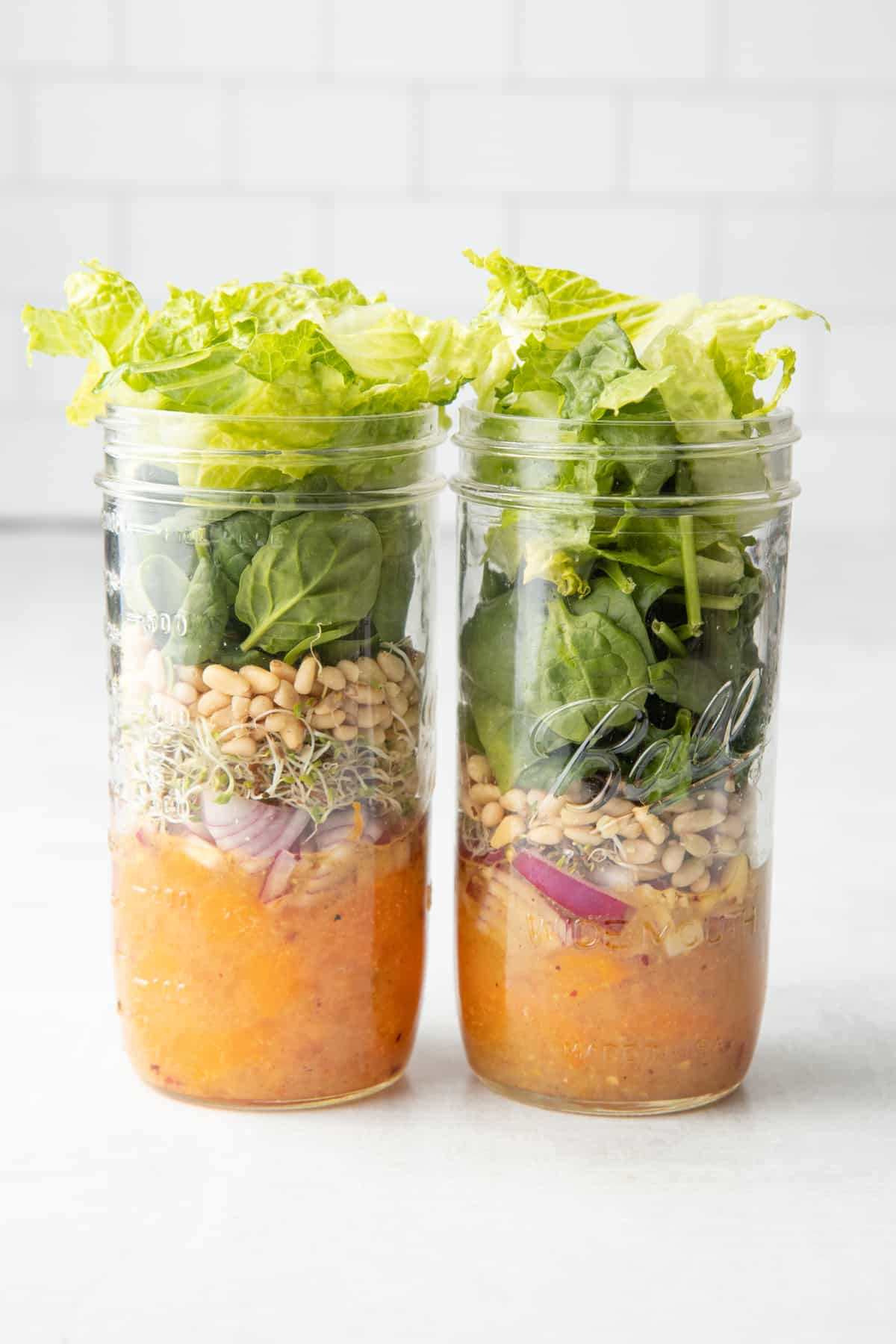 Two jars full of salad components for a citrus salad - dressing, mandarin slices, onions, sprouts, pine nuts, and greens.