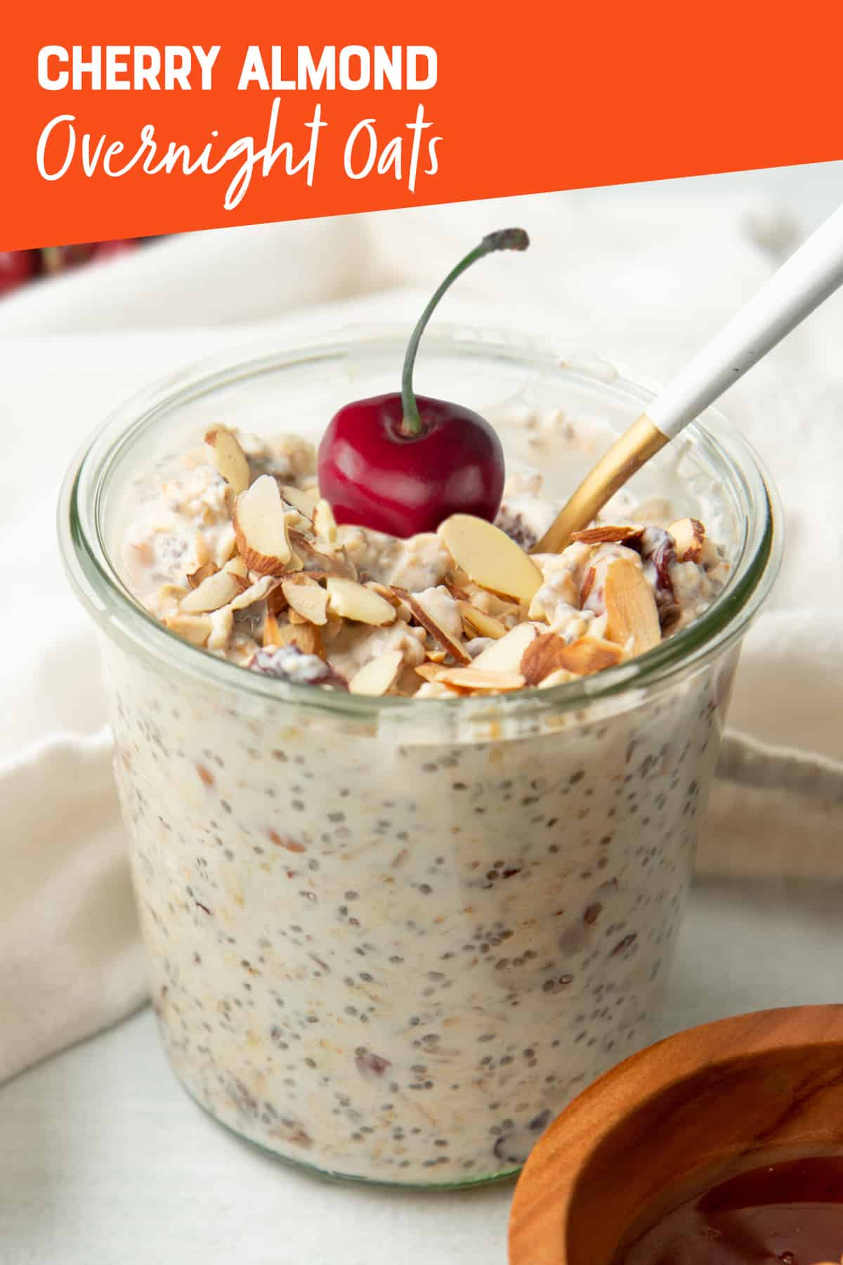 "A spoon rests in a glass jar of cherry and almond overnight oats. The oats are garnished with a whole fresh cherry. A text overlay reads ""Cherry Almond Overnight Oats."""