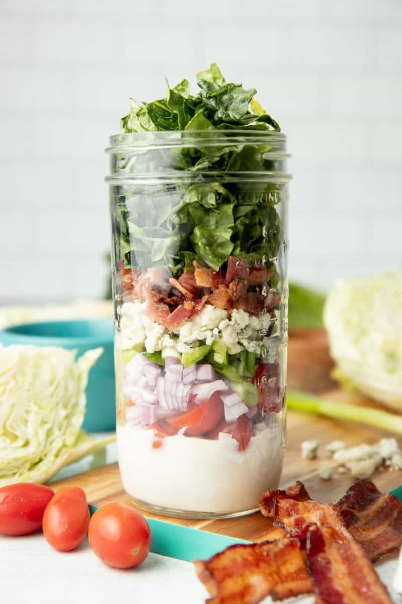 Components of a wedge salad are layered in a glass mason jar, which sits on a teal-edged cutting board. Additional ingredients surround the jar.