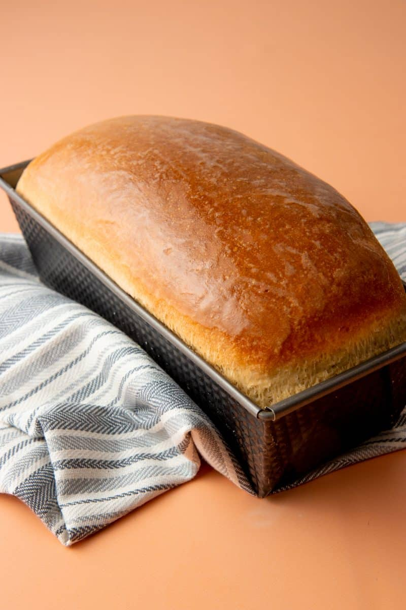 A baked loaf of bread sits in a loaf pan on top of a cloth napkin.