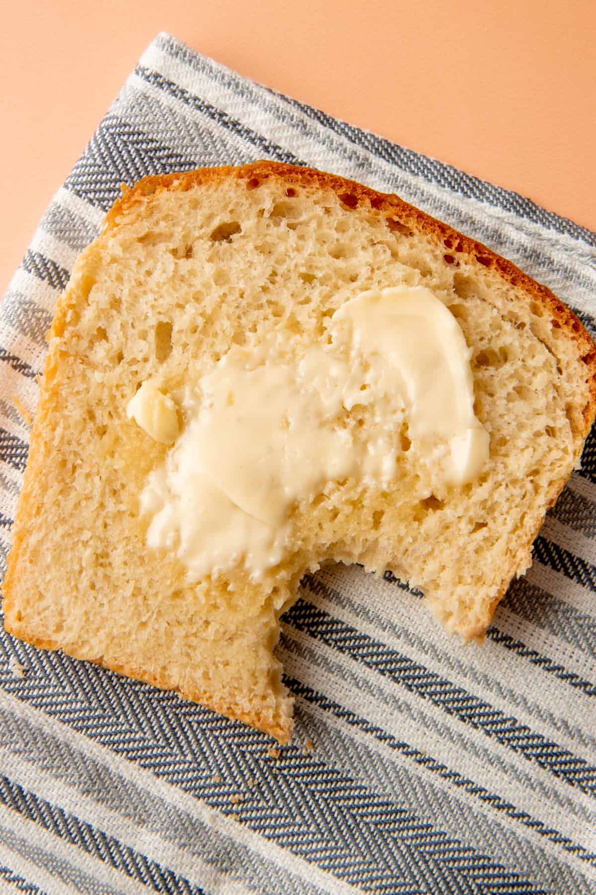 A bitten piece of bread with butter sits on a cloth napkin.