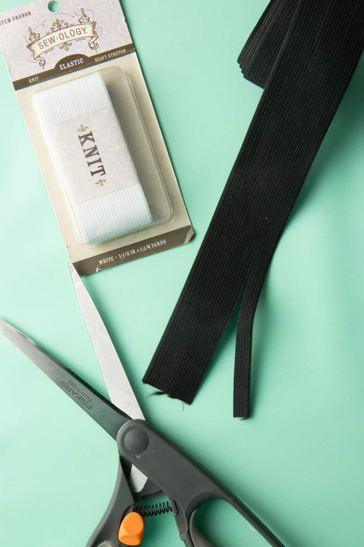 A pack of knit elastic and scissors sit on a green background. An opened portion of black elastic sits in the top left of the image.