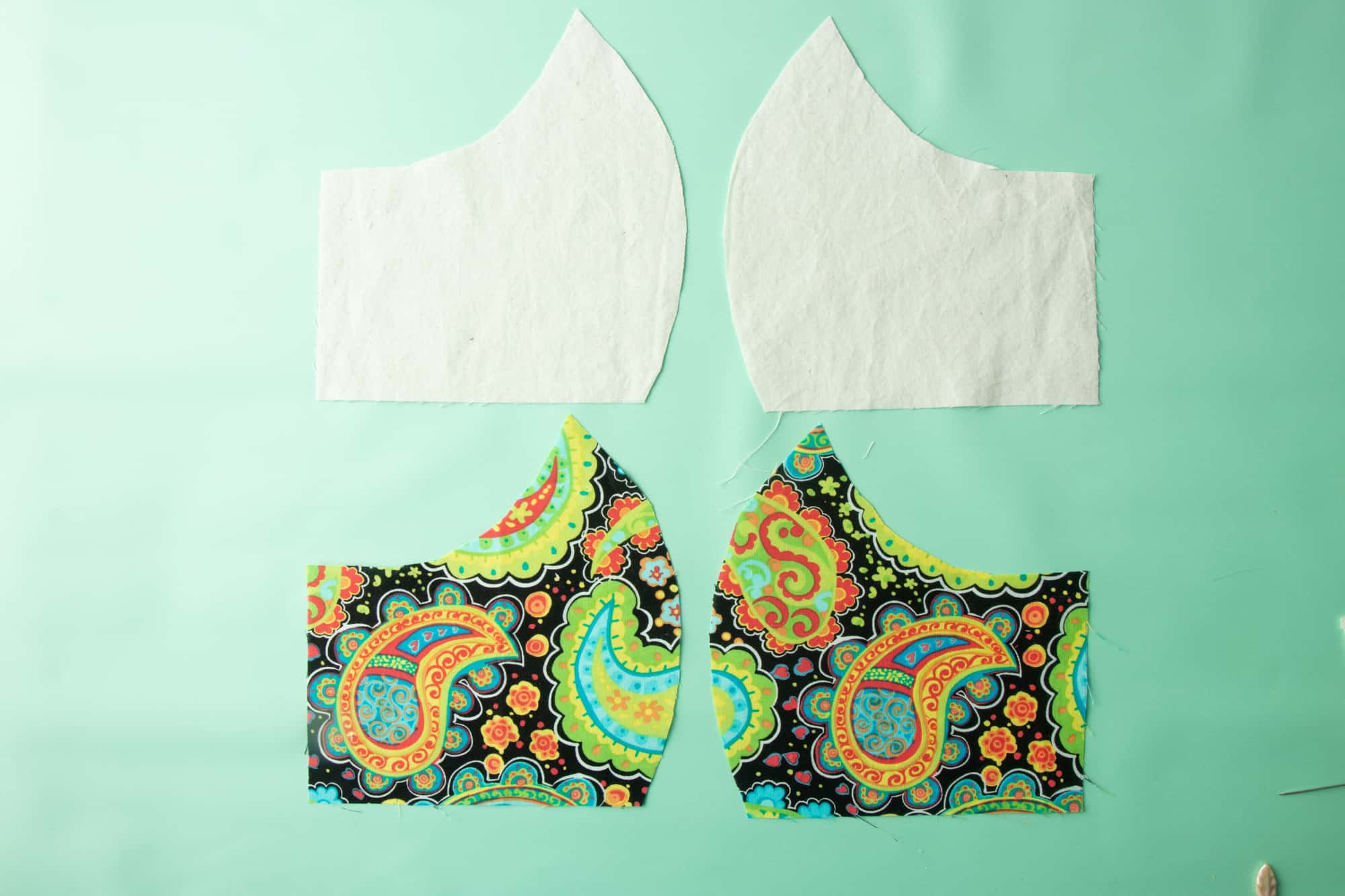 The front and back cut pieces for a face mask lay separately on a green background.