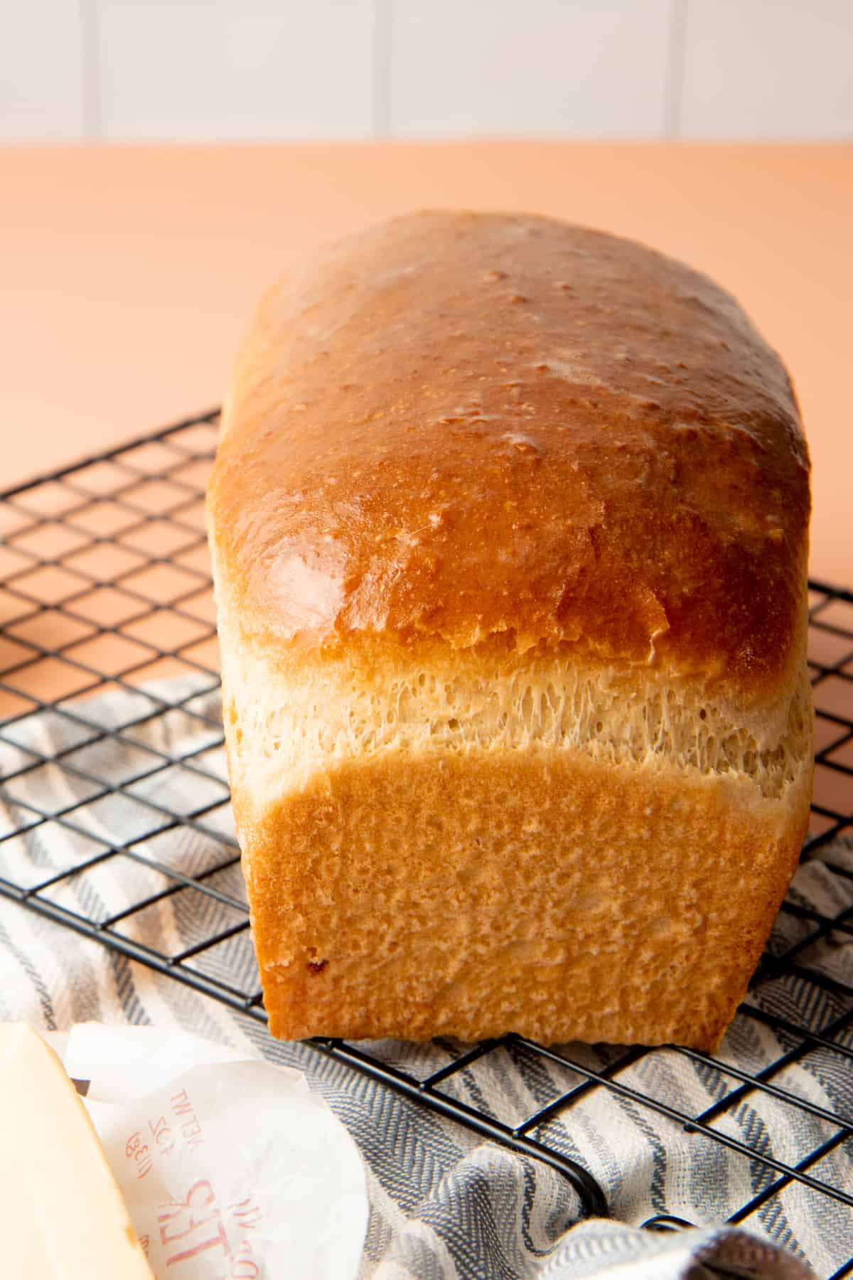 A baked loaf of bread sits on a wire rack.