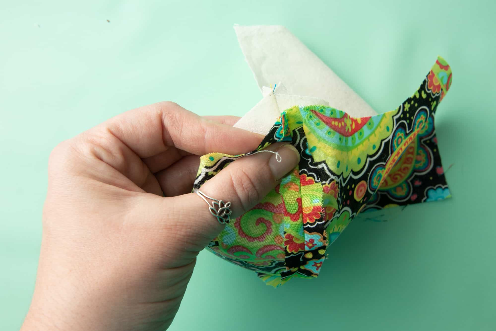 A hand lines up the fabric between the outer and lining pieces of a face mask.