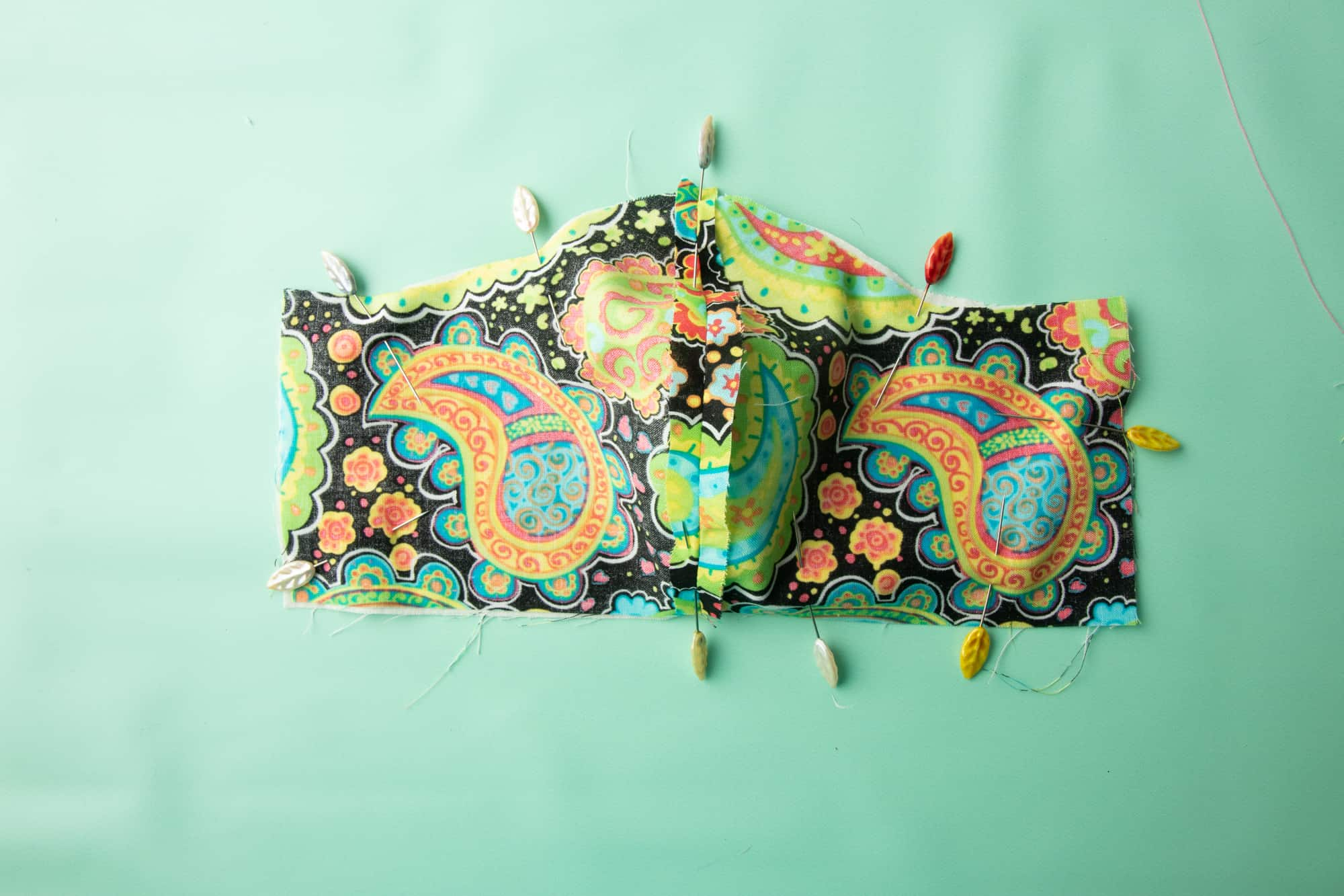 The Face mask sits on a green background with pins holding the front and back fabric pieces together.