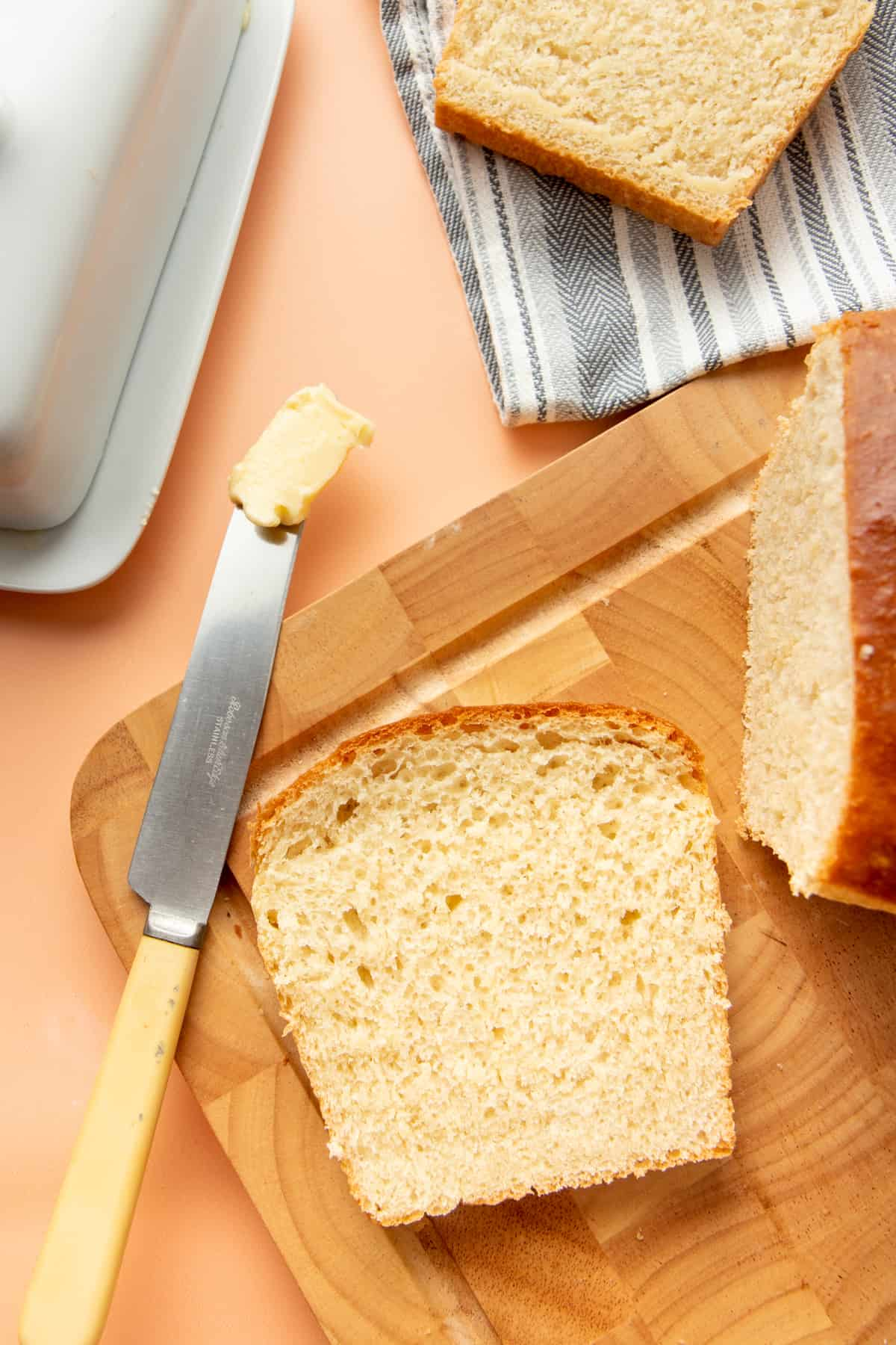 A slice of bread sits on a wooden cutting board next to a knife covered in butter.