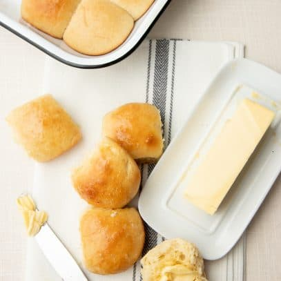 Rolls lay scattered on a fabric napkin, next to a dish of butter. A knife with butter is ready to spread on one of the rolls.