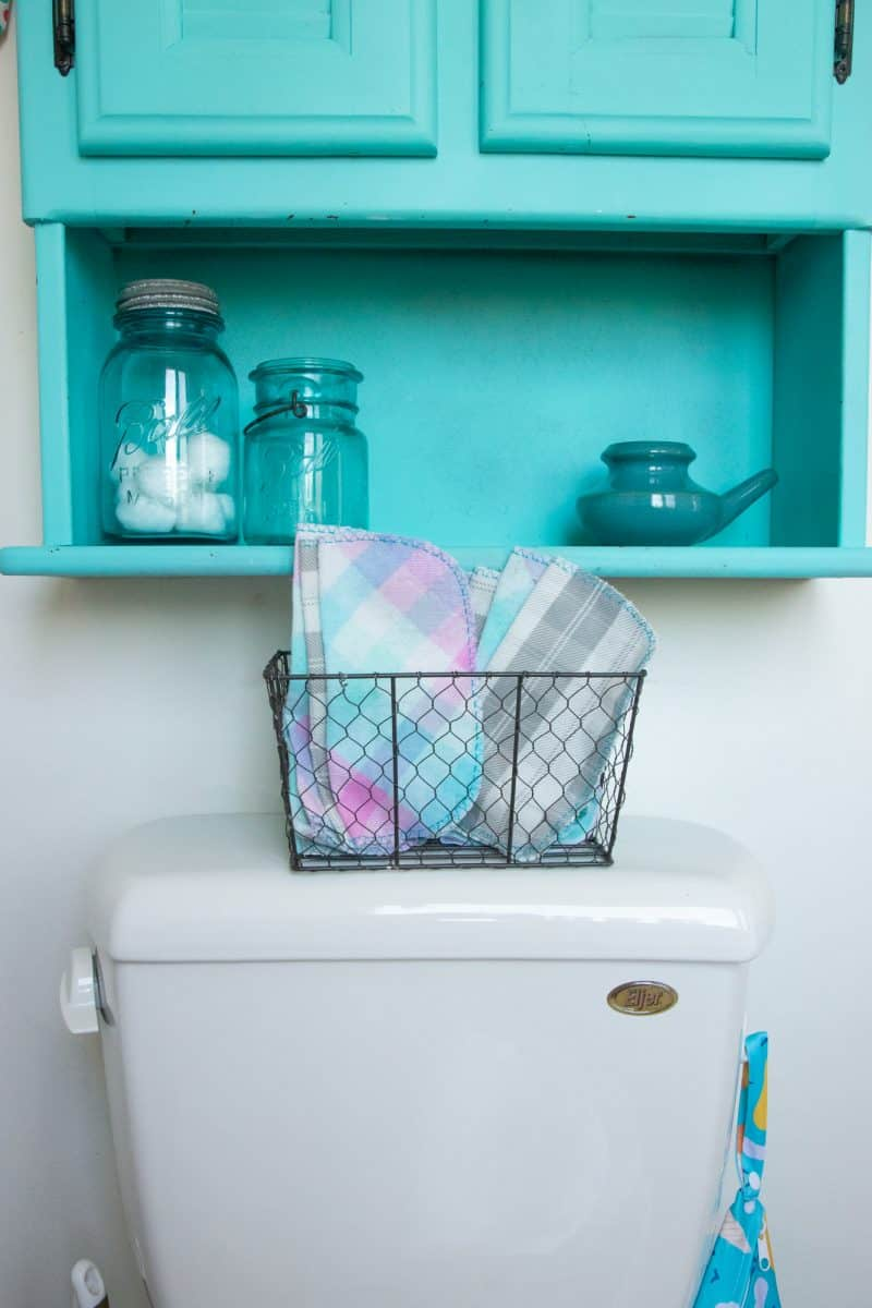 A basket of family cloth sits on top of a toilet. The wet bag hangs to the side of the toilet. A teal cabinet with mason jars on it hangs above the toilet.