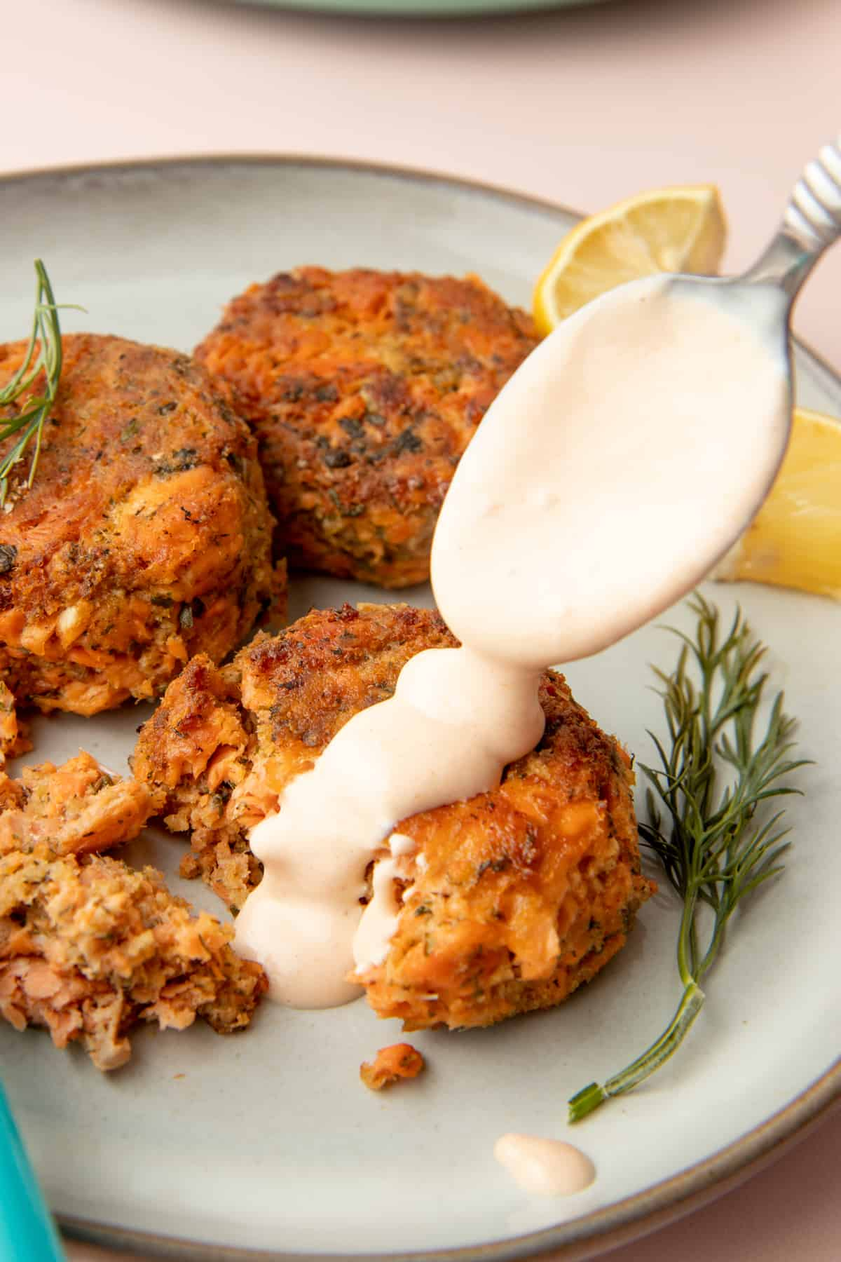 A spoon pours Remoulade Sauce over salmon cakes sitting on a plate. A sprig of dill sits nearby.