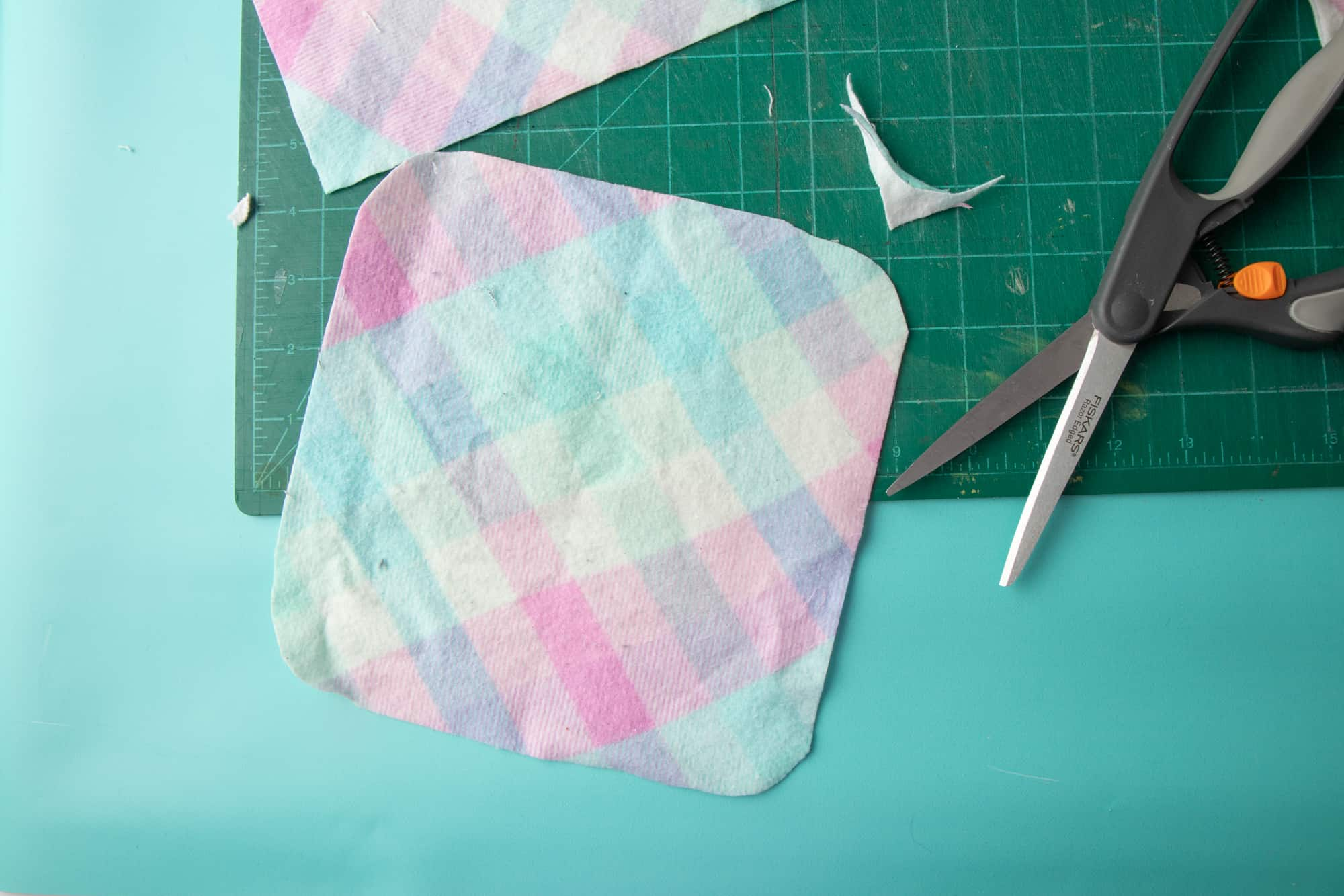 Freshly cut cloth sits on a sewing board on a blue background. A scrap of fabric and scissors sit nearby.