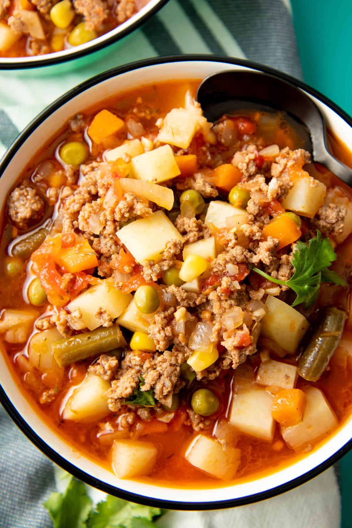 A soup filled with vegetables, potatoes, and beef fills a white bowl with a black rim.