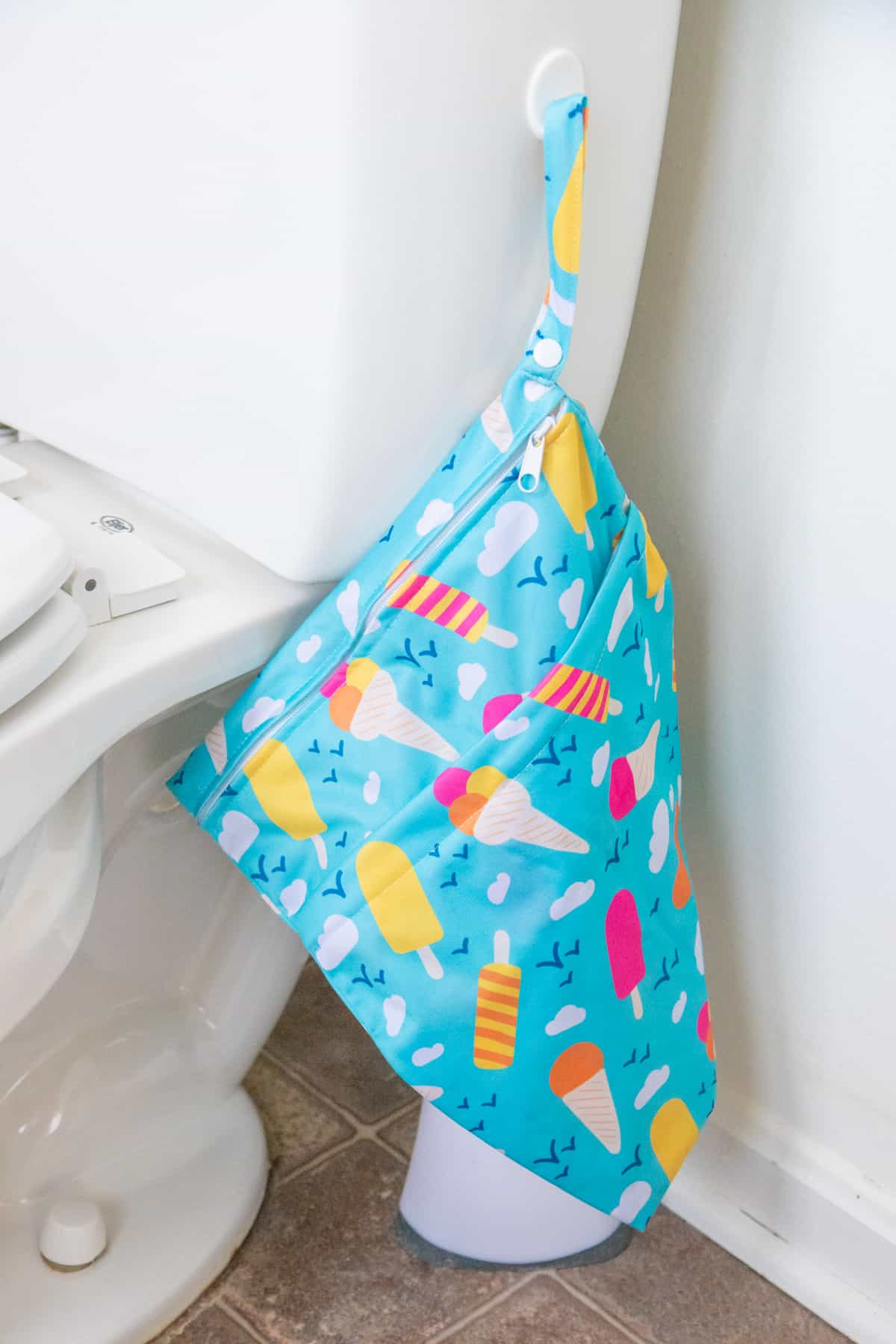 A wet bag hangs on the side of a toilet with a command strip.