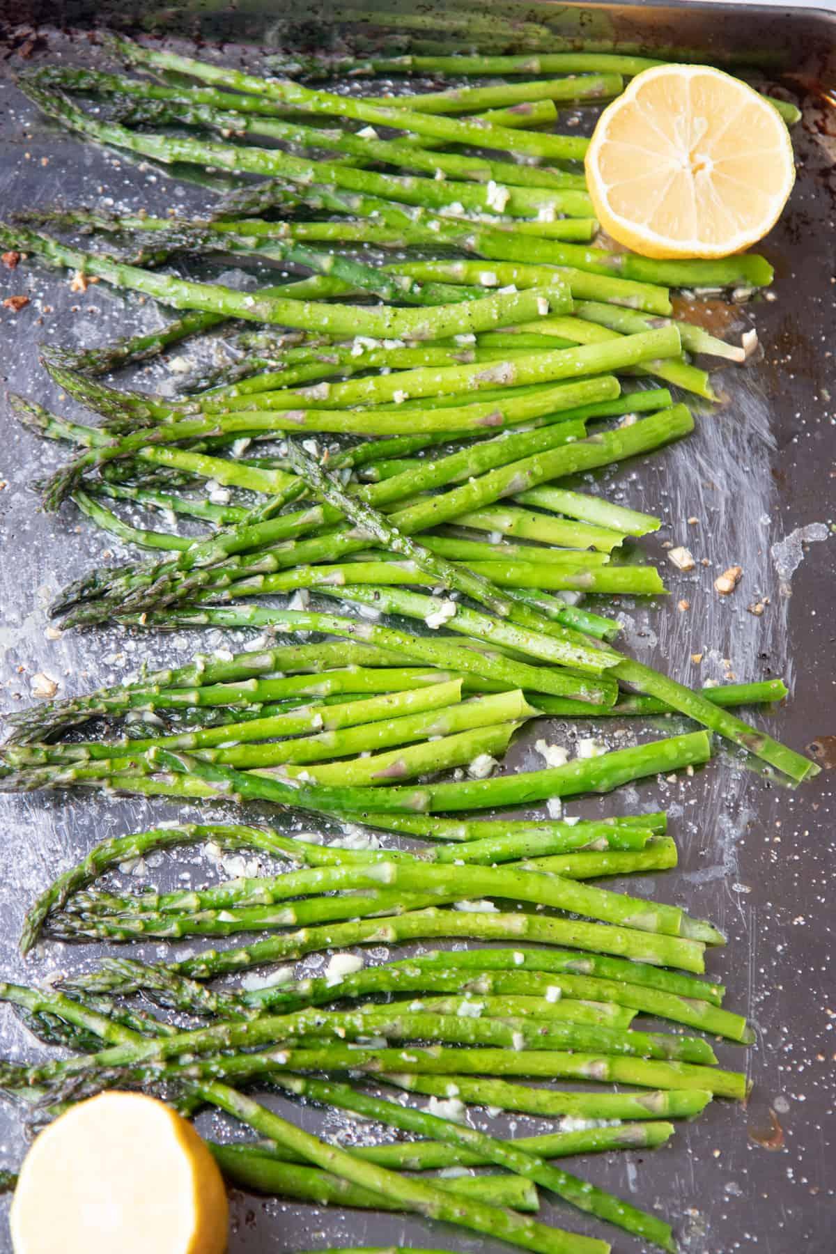 A sheet pan of asparagus, seasoned with garlic and lemon.