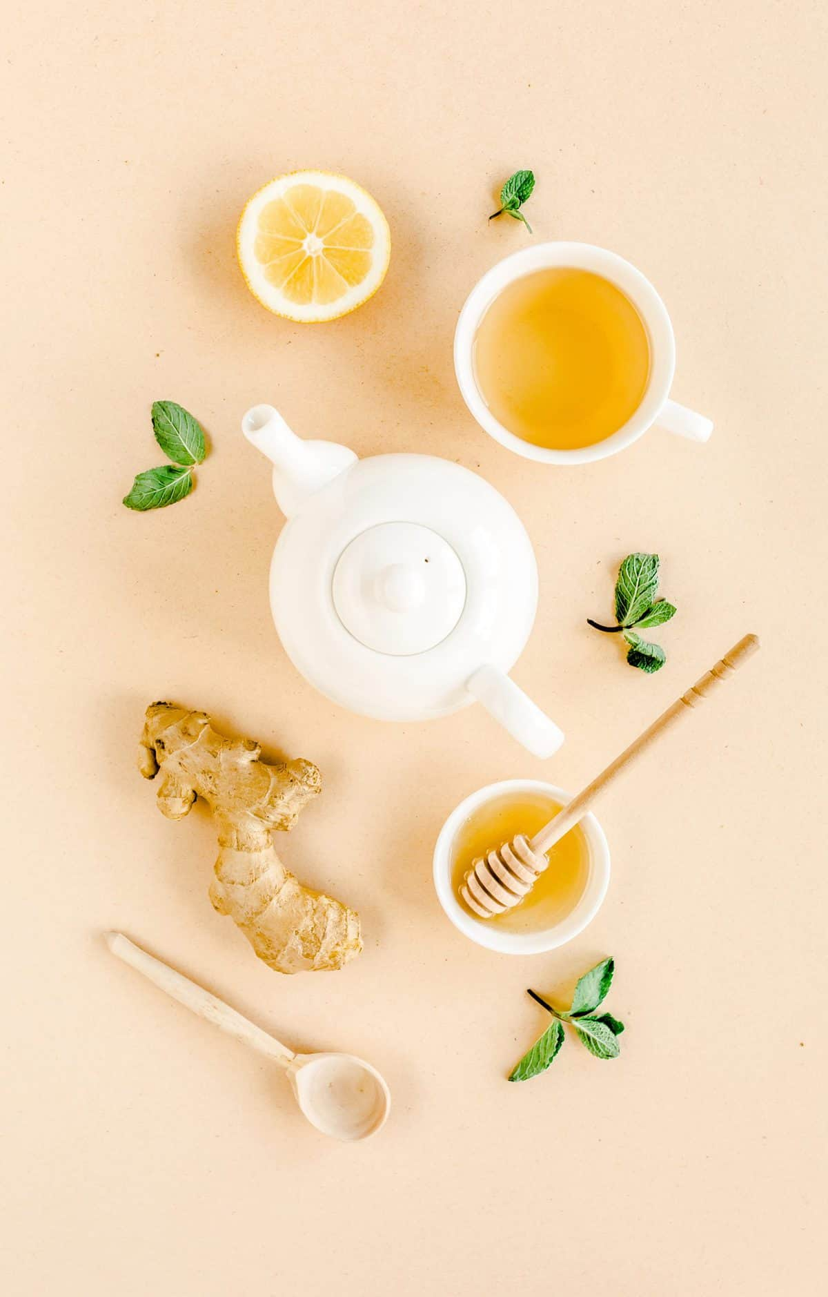 A collage of ingredients to make ginger tea to boost your immune system - honey, ginger root, lemon, tea pot, and a wooden spoon.