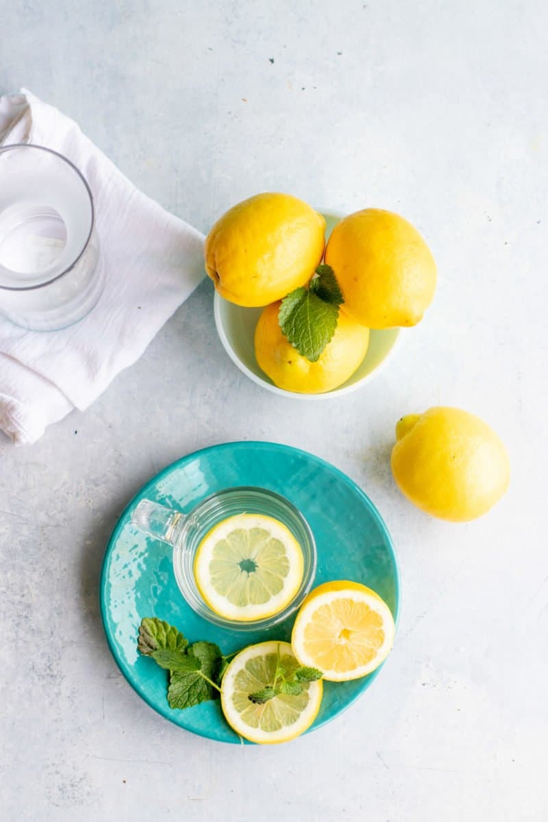 A cup of water sits on a plate with lemons inside of it. A bowl of lemons sits next to it.