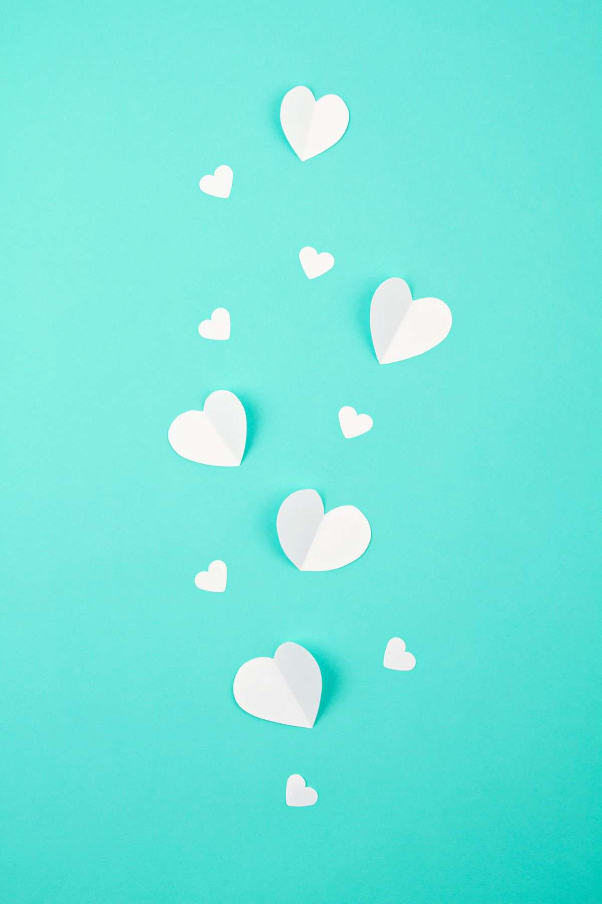 White paper cut out hearts sit on a teal background.