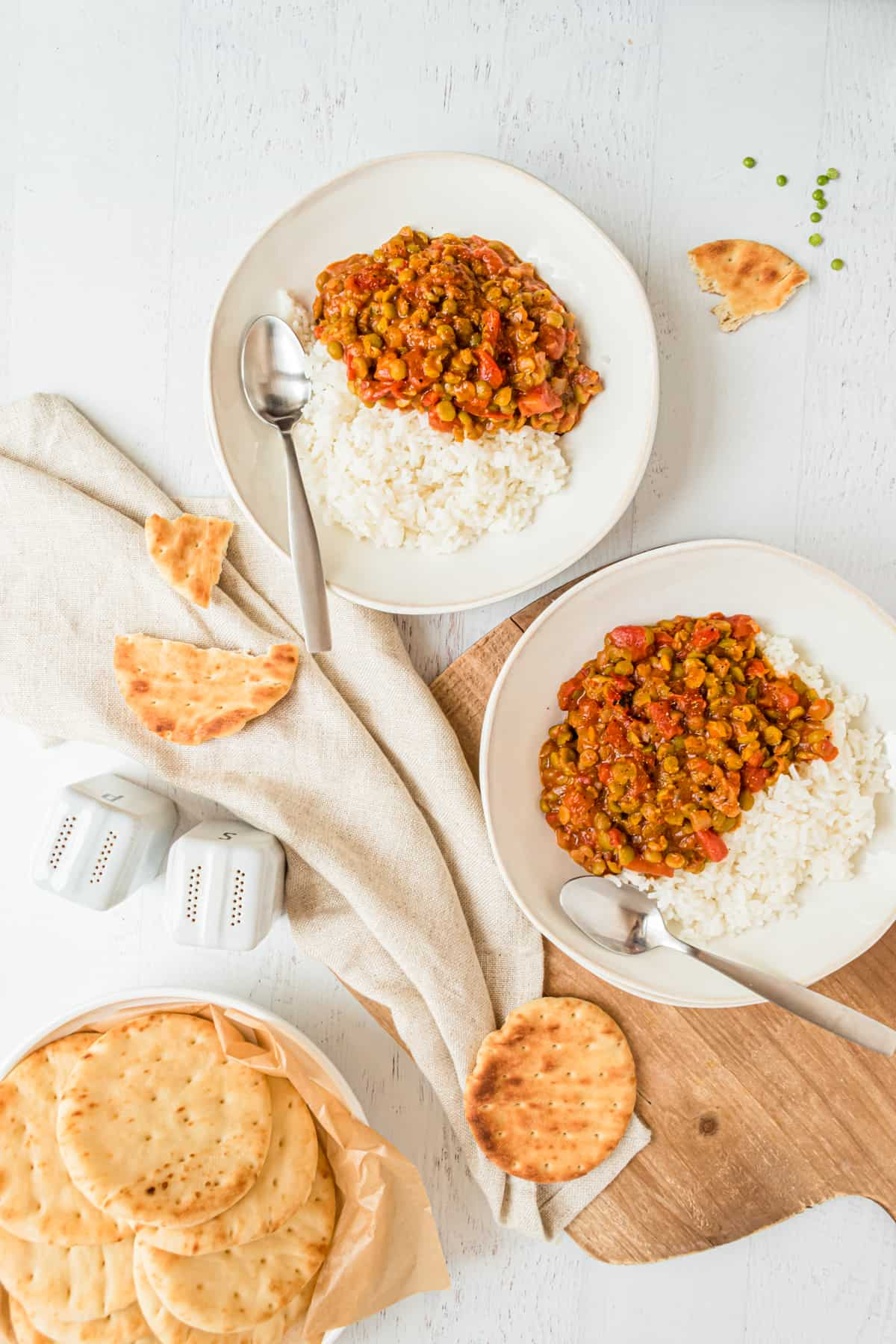 Two bowls of Split Pea Curry sit next to each other with Naan bread nearby.