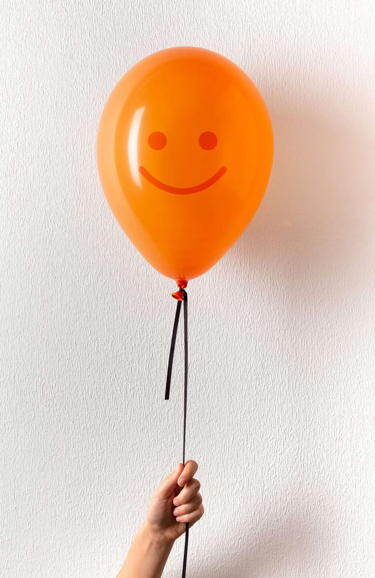 A hand holds an orange balloon, which has a smiley face drawn on it.