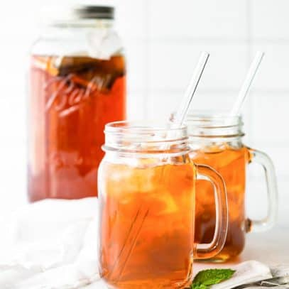 Finished tea over ice in mason jar glasses with handles.