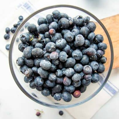 Overhead of individually frozen blueberries in a glass bowl.