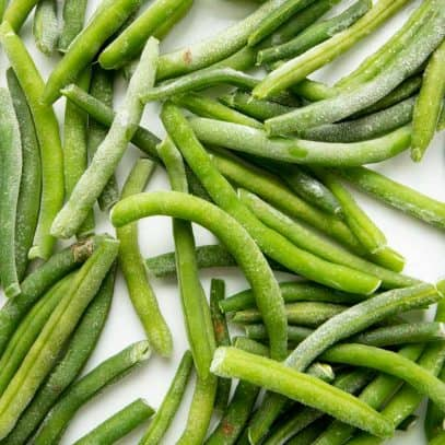 Overhead of individually frozen green beans on a baking sheet.