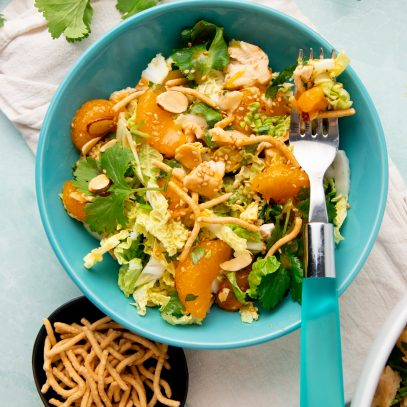 A forkful of mandarin chicken salad rests atop a single serving bowl of salad.