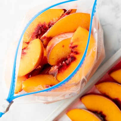 Overhead of open freezer bag filled with individually frozen peach slices.