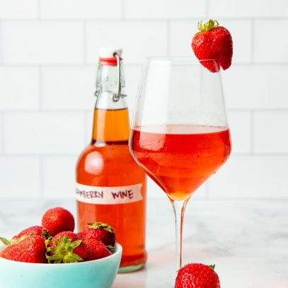 A glass of homemade strawberry wine sits next to a bowl of fresh strawberries.
