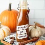 A flip-top glass bottle filled with pumpkin spice syrup sits among decorative pumpkins, cinnamon sticks, and whole star anise.