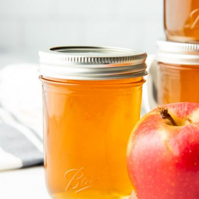 Close-up of a canned jar of apple jelly next to a fresh apple.