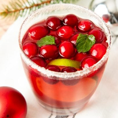 Close-up of a glass of holiday punch surrounded by Christmas ornaments and pine branches.