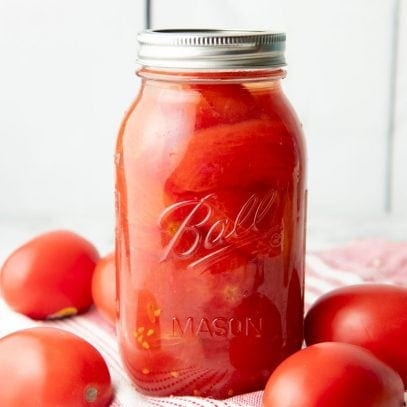 A jar of canned whole tomatoes sits atop a kitchen linen surround by fresh tomatoes.