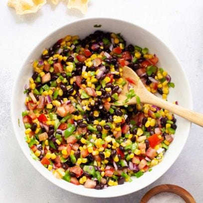 Overhead of a white serving bowl with black bean and corn salsa and a wooden spoon in it.