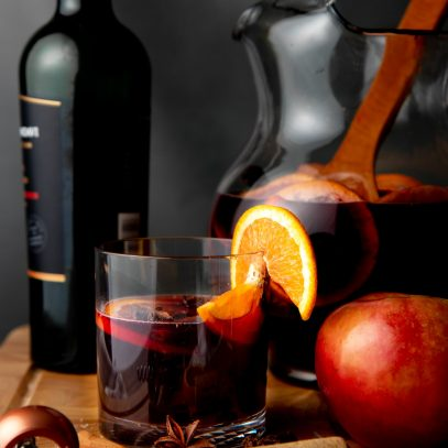 A rocks glass of apple cider sangria sits on a wooden cutting board in front of a bottle of red wine and pitcher of sangria.