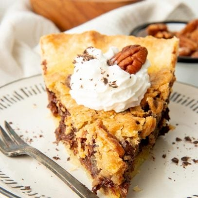 Front view of a single slice of bourbon pecan pie on a white plate.
